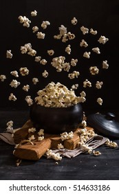 Popcorn exploding inside the clay pot on a dark background