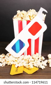 popcorn with glasses and tickets on wooden table on grey background