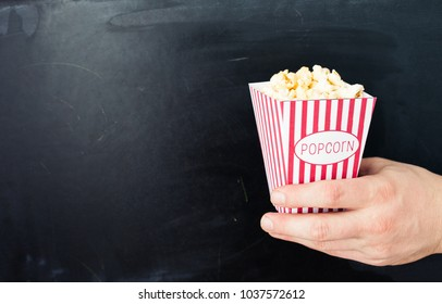 Popcorn in a hand on a chalkboard background with copy space.Movie night.Cinema concept.Popcorn mockup.Place for text.