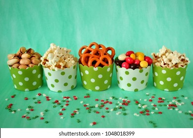 Popcorn, multicolored drops, pretzels with salt and pistachio nuts in paper cups on green background. Snacks assortment