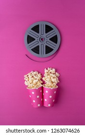 Popcorn in multiple carboard boxes and film roll over pink background