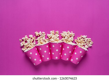 Popcorn in multiple carboard boxes over pink background