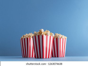 Popcorn in multiple carboard boxes over blue background