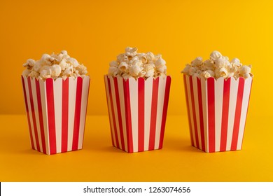 Popcorn in multiple carboard boxes over yellow background