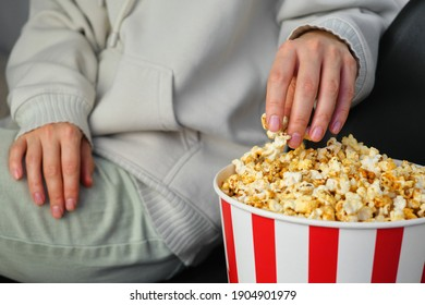 Popcorn paper bucket in the hands of a young girl preparing to watch a movie. Showtime. Eating delicious unhealthy sweet snacks. Going to cinema for a new film. Rest and entertainment. Popcorn closeup