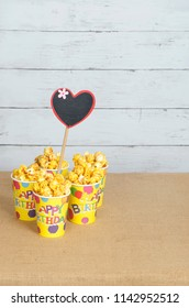 Popcorn in paper cup with wooden love sign