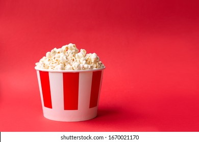 popcorn in a paper striped box on a red background with copy space. American food background. Red background. Fast food.