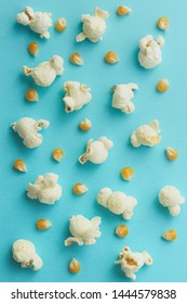 Popcorn pattern arranged with fresh white popped popcorn and yellow raw corn seeds on light blue background