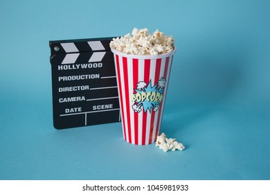 Popcorn pot with clapperboard on blue background