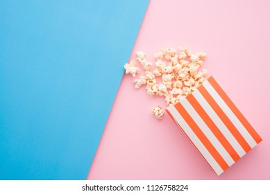 Popcorn in red bag on colorful blue pink background, flatlay still life minimal style