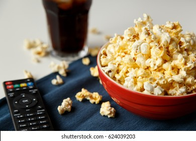Popcorn in red bowl with tv remote and cola in background.