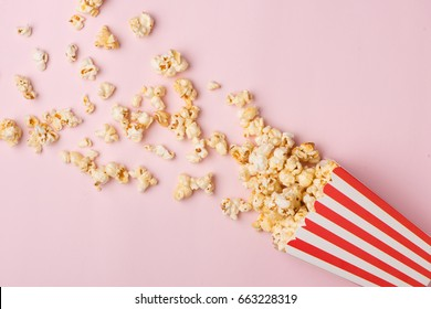 Popcorn in red and white cardboard box on the pink background.