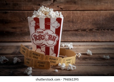 Popcorn in red and white cardboard box with tickets on a wooden background