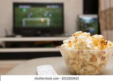 popcorn and remote control on sofa with a TV broadcasting soccer match on background