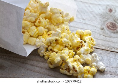 Popcorn spilling from plain white bag onto picnic table