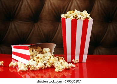 Popcorn in a striped box. Movie eating in theater