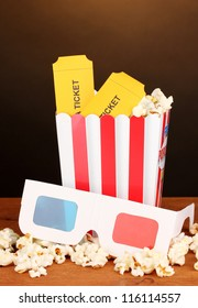 popcorn with tickets and cinema glasses on wooden table on brown background