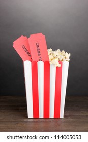 popcorn with tickets on wooden table on grey background