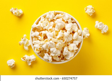 Popcorn viewed from above on yellow background. Flat lay of pop corn bowl. Top view