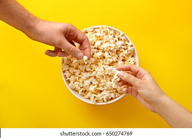 Popcorn viewed from above on yellow background. People eating popcorn. Human hands. Top view