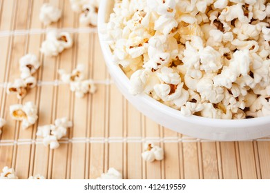 popcorn in a white bowl and spilled on the mat