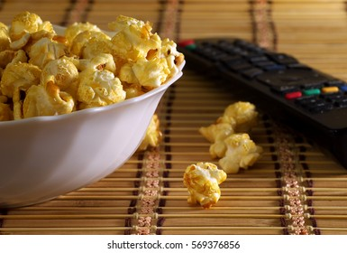 popcorn in a white bowl and tv remote, shallow depth of field, selective focus.
