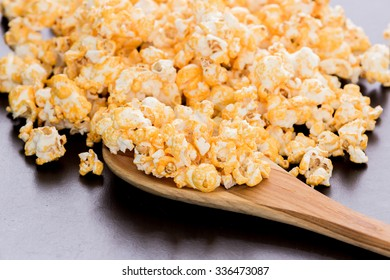 popcorn and wooden ladle scoop on wooden table.