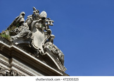 Pope emblem between angels at the top of Ss Luca and Martina baroque church in Rome, designed by Pietro da Cortona in the 17th century (with copy space)