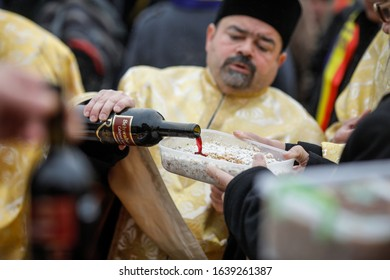 Popesti Leordeni, Romania - December 20, 2019: Shallow depth of field (selective focus) image with an orthodox priest pouring wine on a funeral cake during a ceremony.