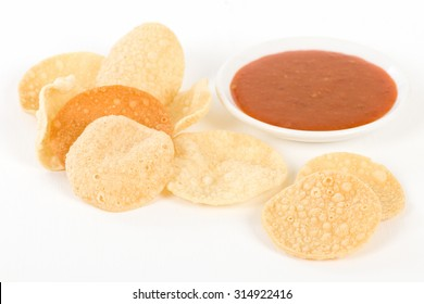 Poppadoms - Fried mini poppadoms in a on a white background. Served with chilli sauce.