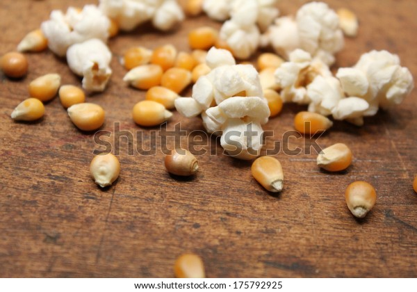 Popped popcorn and kernels over wood background