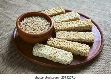 Popped quinoa seeds in bowl with quinoa cereal bars, one with honey the other mixed with amaranth, photographed with natural light (Selective Focus, Focus into the middle of the popped quinoa seeds)