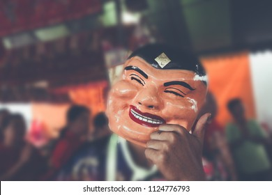 Popper smiling mask in Chinese new year lion dance shows . old man chinese with blur background color vintage style.