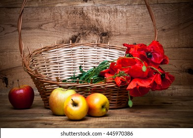 Poppies in basket and apples on wooden background