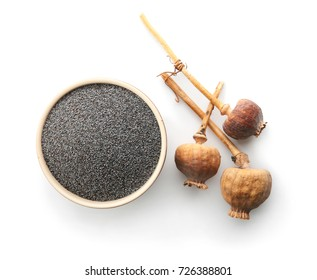 Poppy seeds and dried pods on white background