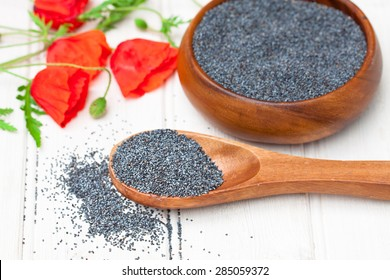 poppy seeds in a wooden bowl on a table with spoon