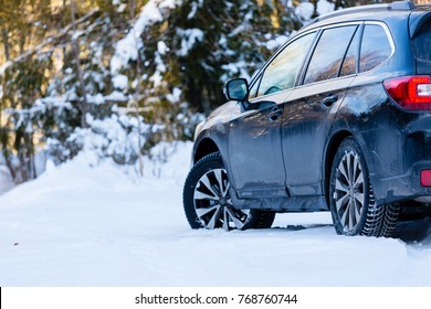 Poprad, Slovakia - November 30, 2017 : Winter tires. Black Subaru Outback rear view on snowy forest road. Winter conditions.
