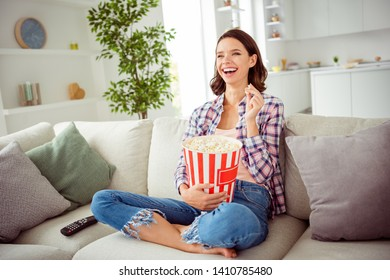 Poprtarit of cute funny funky lady sit divan legs crossed folded laughter content cheerful funny funky serials sitcoms wavy curly hairdo shirt checkered plaid jeans apartment