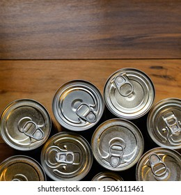 Pop-top processed and sealed food cans, tin and steel easy open, packaged containers grouped together at the bottom of the image on an isolated wood textured background.