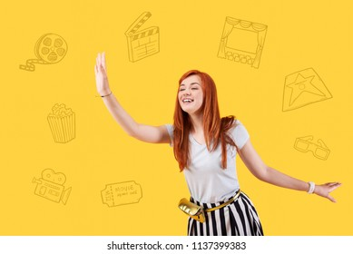 Popular actress. Cheerful famous actress feeling glad and smiling while visiting a big cinema and waving to her fans