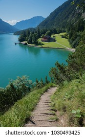 popular adventure trail along the lakeside of achensee, with view to gaisalm hut, austrian spring landscape