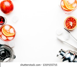 Popular alcoholic cocktail Negroni with dry gin, red vermouth and red bitter, orange and ice cubes. White background, bar tools, top view, place for text.