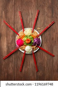 """Popular among Malaysia and Singapore region Chinese new year raw fish salad """" Yu Sheng"""" on rustic wooden table top. Flat lay food image."""
