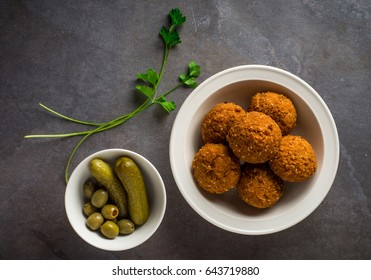 A popular arabic snack - Falafel. A bowl full of fried Falfel with pickle and strands of green parsely.