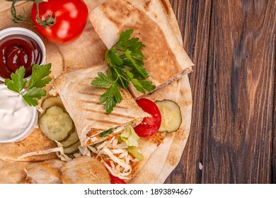 Popular arabic turkish fastfood doner shawarma roll with meat and vegetables and ingredients on wooden background. top view