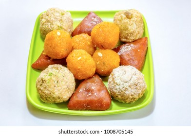 Popular Bengali sweets namely Darbesh, Chitrakoot and Joynagarer moa displayed on a plate. These Indian sweetmeat delicacies are primarily prepared from farmers cheese, date palm and flour.