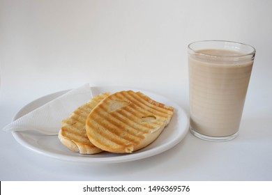 Popular brazilian bread with melted butter called pao na chapa and a glass of hot coffee mixed with milk called media or pingado found in any bakery on a white background