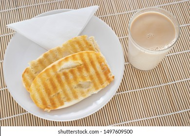 Popular brazilian bread with melted butter called pao na chapa and a glass of hot coffee mixed with milk called media or pingado found in any bakery on a bamboo mat background