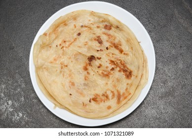 Popular breakfast dish Kerala Parotta or Porotta is a layered flatbread made from maida flour, served in organic plate or platter in South India. Delicious with side dish chilli chicken or chilli beef