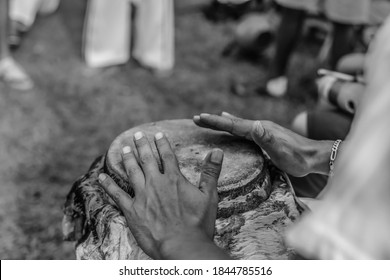 Popular capoeira culture - Hands of man playing African percussive drum in black and white